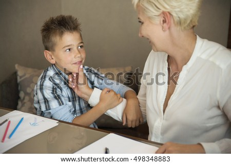 Smiling woman with young son sitting at a desk