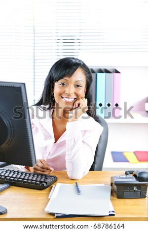 Smiling young black business woman at desk in office