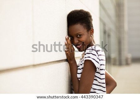 smiling young black woman in striped shirt standing outside