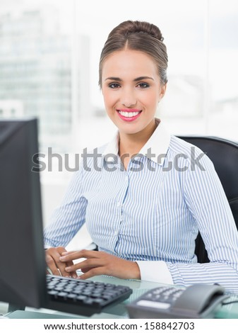Smiling young businesswoman sitting in front of computer in bright office