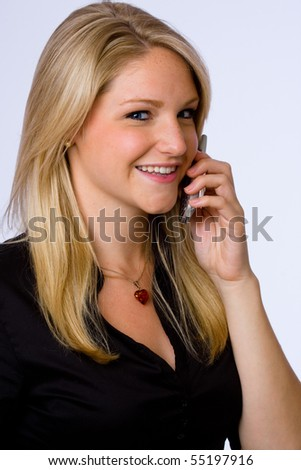 Smiling young businesswoman talks on cell phone.