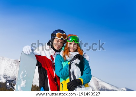 Smiling young couple with snowboards