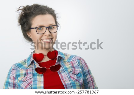 Smiling young girl with eyeglasses and two sunglasses in the form of hearts in a white background