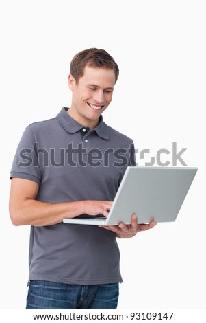 Smiling young man working on laptop against a white background