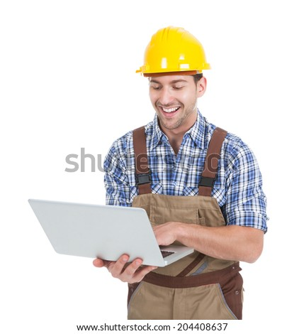Smiling young manual worker using laptop over white background