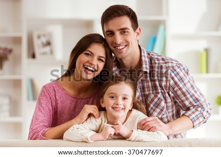 Smiling young parents and their child are very happy, they are at home