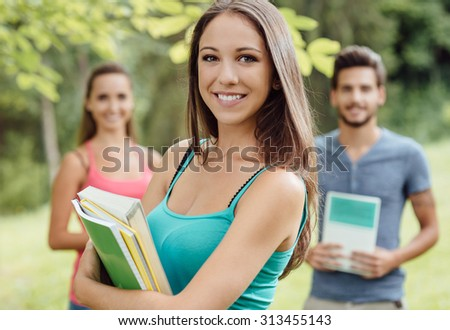 Smiling young student at the park holding books and notebooks, her friends are standing on background