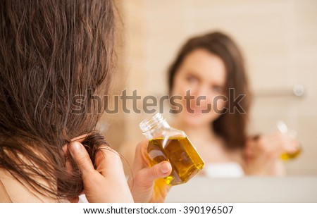 Smiling young woman applying oil mask to hair tips in front of a mirror; haircare concept