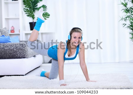 Smiling young woman doing exercise at her home.