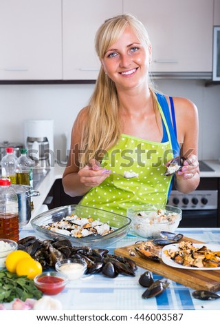 Smiling young woman filling shells with rice and mussels meat at home kitchen