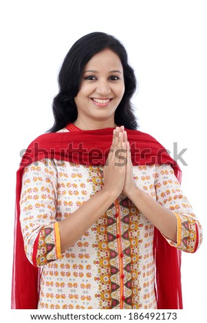 "Smiling young woman greeting ""Namasthe"" against white background"