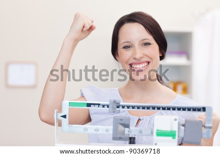 Smiling young woman happy about what the scale shows