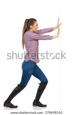 Smiling young woman in jeans, black boots and lumberjack shirt pushing a white wall. Side view, full length studio shot isolated on white.