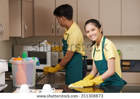 Smiling young woman wiping tabletop when man cleaning microwave