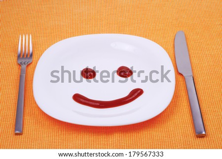 Smilling face made of ketchup on the plate