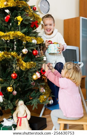 Smilling sisters helping each other to decorate New Year tree in apartment