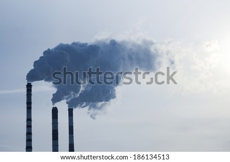 Smoke emission from factory pipes on blue sky
