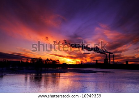Smoke stack from manufacturing plants at sunset in winter