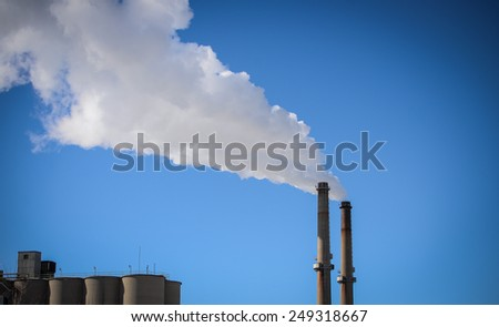 Smoke stacks with white smoke against a bright blue sky in Milwaukee,WI