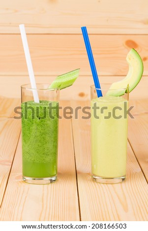 Smoothies of cucumbers and melon. Located on wooden background.