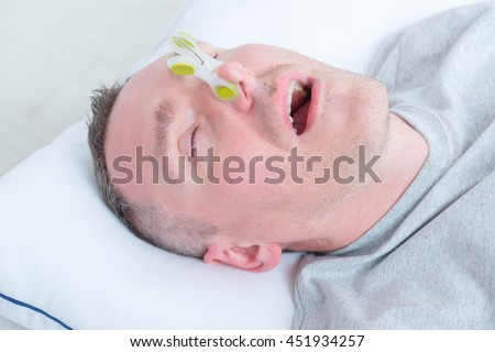 Snoring man in bed with cloth clip on his nose