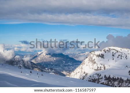Snow-covered mountains in the French Alps with a slope in the foreground, sunlight and also some grey clouds in the background.