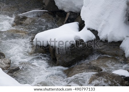 snow hat with icicles on a stone in a creek in winter