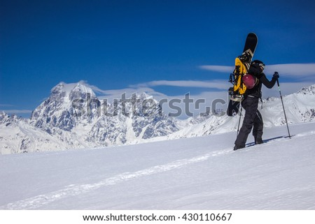 Snowboarder goes uphill with his snowboard on the back with the blue sky and Ushba mountain in background