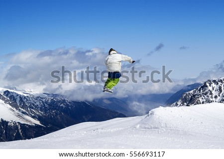 Snowboarder jumping in terrain park at ski resort on sun winter day. Caucasus Mountains, region Dombay.