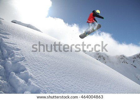 Snowboarder jumps on winter mountain.
