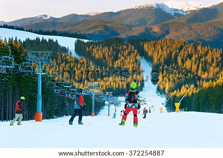 Snowboarders on a mountains slope at ski resort at sunset