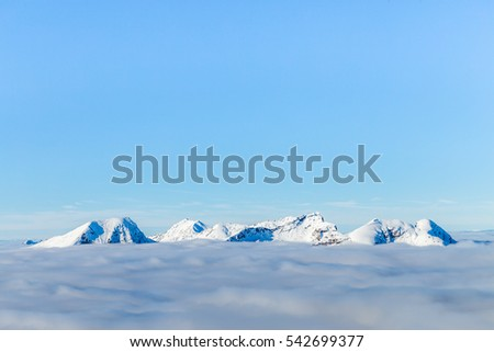 Snowcaped mountain tops peaking above the clouds