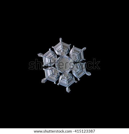 Snowflake isolated on black background: macro photo of real snow crystal, captured on glass surface with LED back light. This is medium size snowflake with amazing relief surface and symmetry.