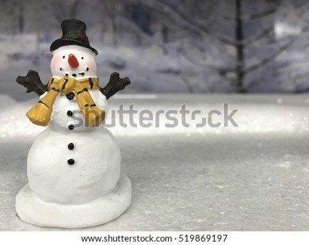 Snowman Figure with yellow scarf on white surface