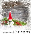 Snowman with the branches of fir on a snowbound wooden background - stock photo