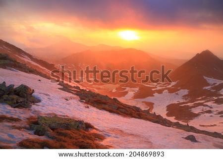 Snowy mountains under foggy clouds at sunset