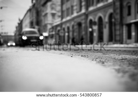 Snowy winter in the big city, on the snowy street going cars. Close up view from the road level, image in the black and white tones