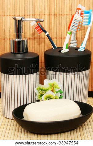 Soap dispensers with toothbrushes and bar on bamboo background.