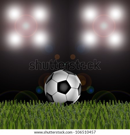 Soccer ball on the green field and stadium spotlight