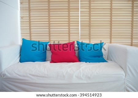 Sofa with blue and pink pillows in room