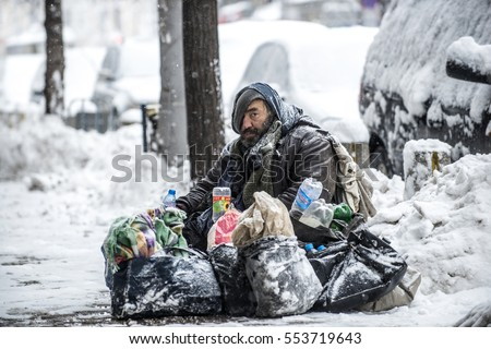 Sofia, Bulgaria - January 6, 2017: homeless hobo sitting on snow street in the city center with their hand luggage.