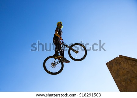 Sofia, Bulgaria - September 24, 2016: Silhouette of a biker jumping against the blue sky and the sun.