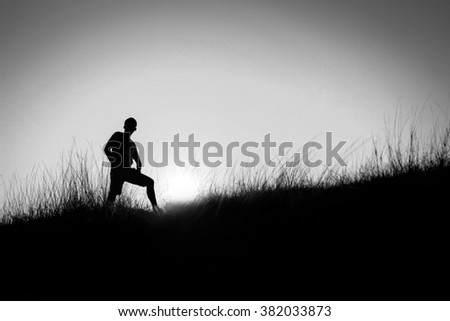 soft focus black and white  Silhouette of a man at the beautiful sunset on the wilderness mountain. Background