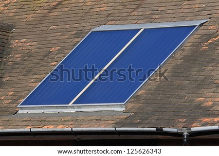 Solar glass hot water panel array mounted on a tiled roof