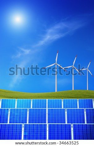 Solar panels and wind turbines against green field and blue sky with sun