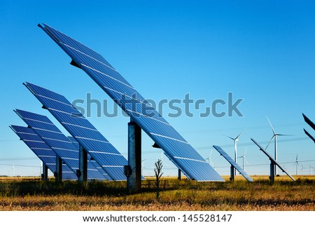 Solar panels farm and wind turbines at background under a blue sky.