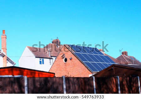 Solar panels for electricity generation on brick house roof in Esssex. England. Solar panels installed on domestic roof. Different style of English house with blue sky in winter season.