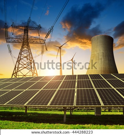 Solar panels in the background nuclear power plant, wind turbines and electricity pylon at sunset. Concept of energy resources.