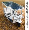 Solar powered tuc tuc parked on an autumn leaf covered spot in a park - stock photo