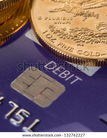 Solid gold coins contrasted with debit word on plastic credit card suggesting debt problems